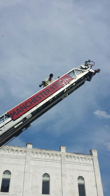 Taking photos from a ladder of a fire truck.
